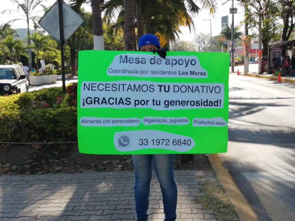 Mujer sosteniendo un cartel con el número de contacto de grupo altruista Vallarta sin Hambre